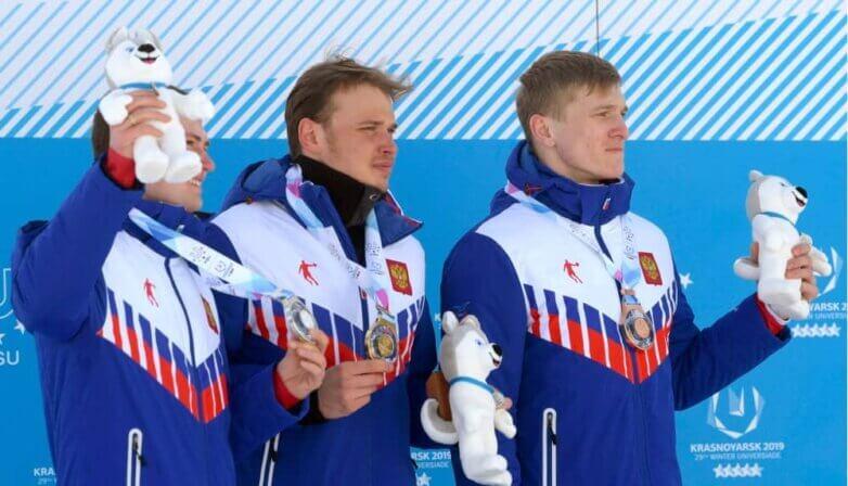 Антон Тимашов (серебро), Иван Якимушкин (золото), Иван Кириллов (бронза) во время церемонии награждения призеров лыжных гонкок на 10 км