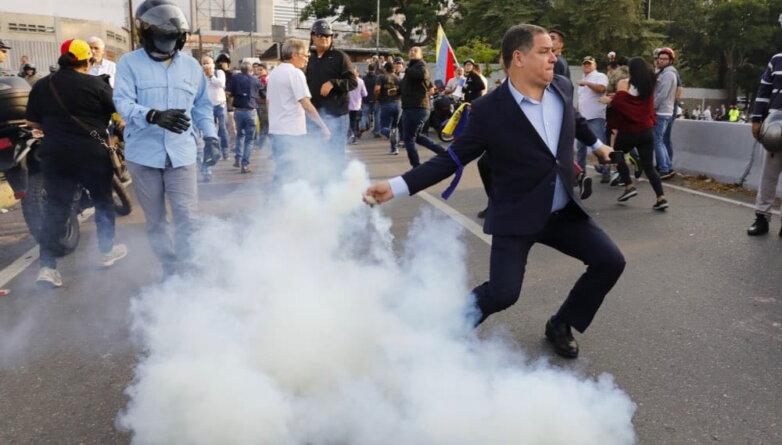 Венесуэла. Каракас. Противник президента Венесуэлы Николаса Мадуро перебрасывает обратно шашку со слезоточивым газом, брошенную со стороны авиабазы Ла-Карлота (имени Франсиско де Миранды).