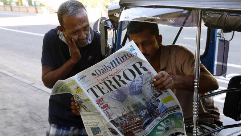 Шри-Ланка, местные жители читают прессу о терактах