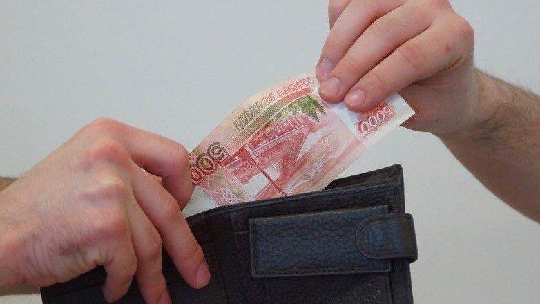Руки тянут деньги из кошелька