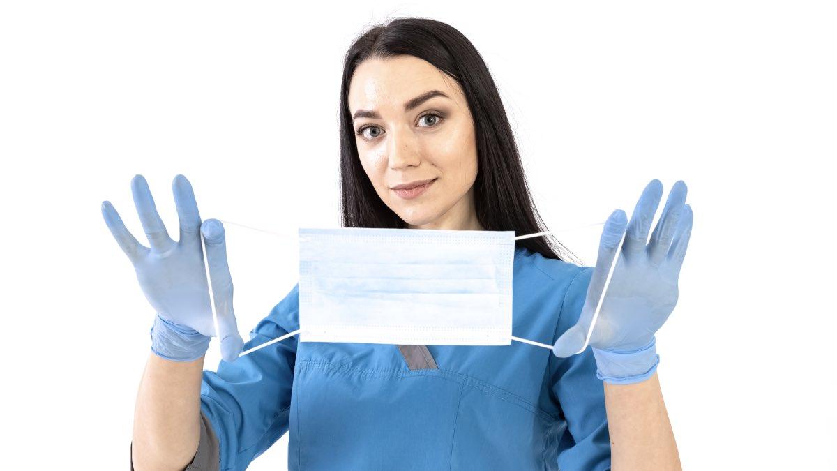 врач показывает медицинскую маску