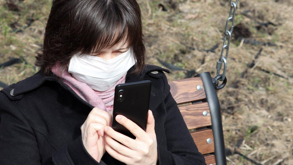 женщина в маске со смартфоном