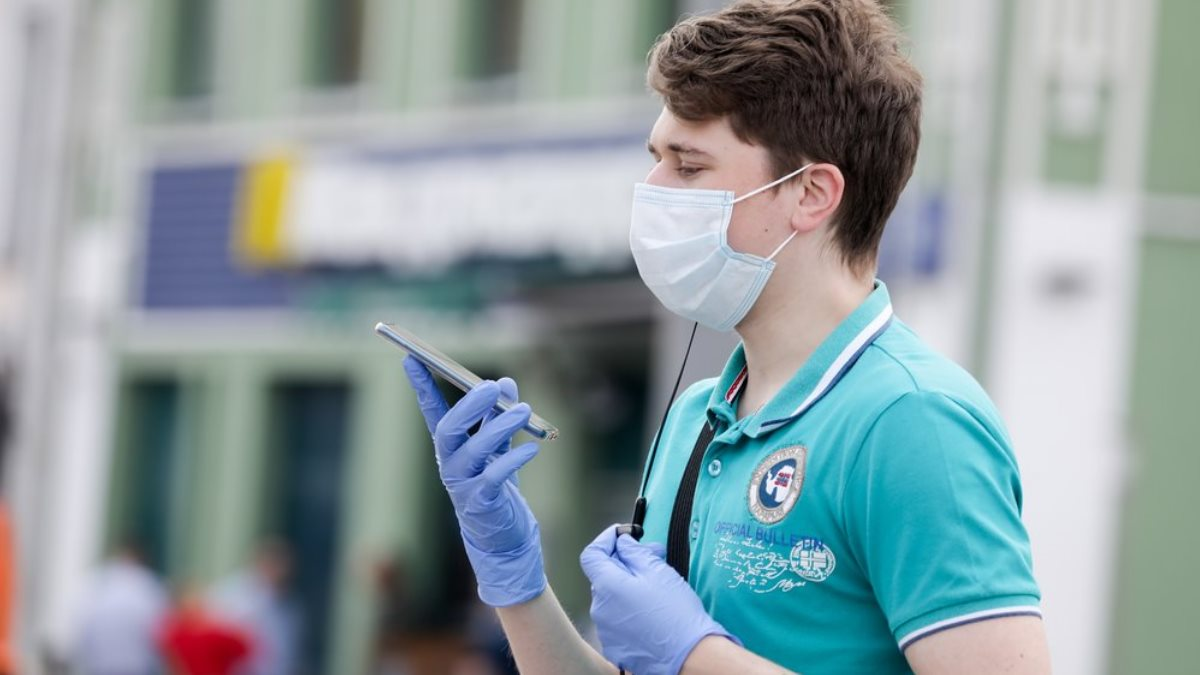 Коронавирус улица парень с телефоном маска перчатки