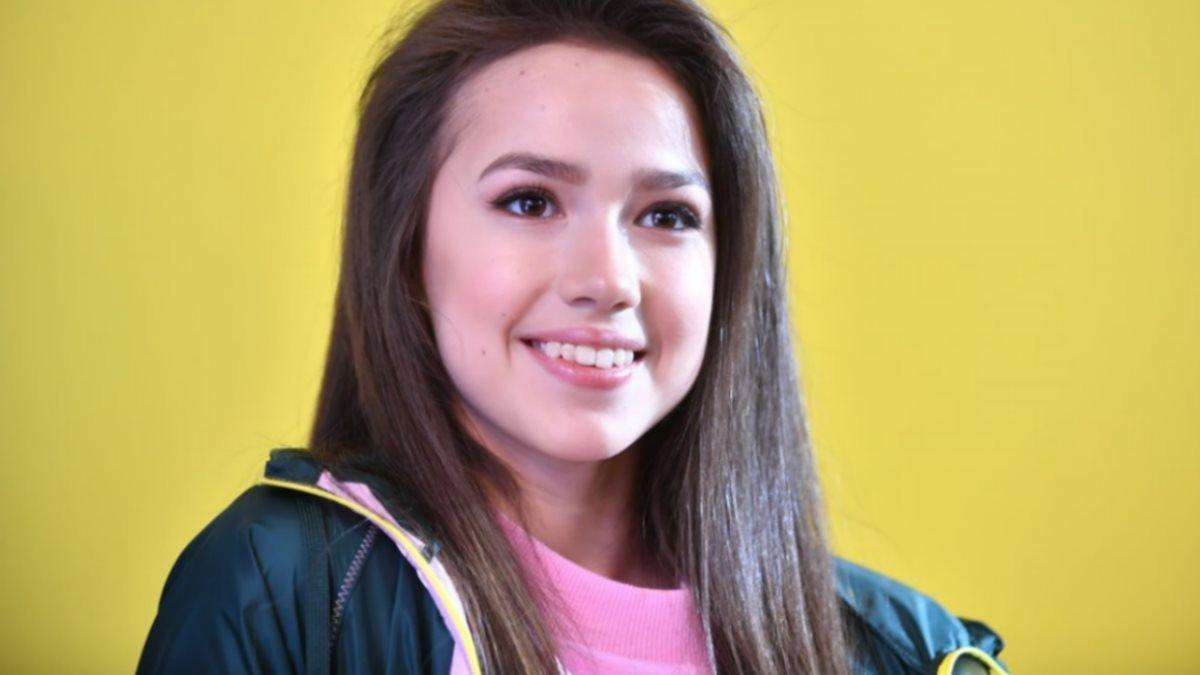 Фигуристка Алина Загитова улыбается жёлтый фон