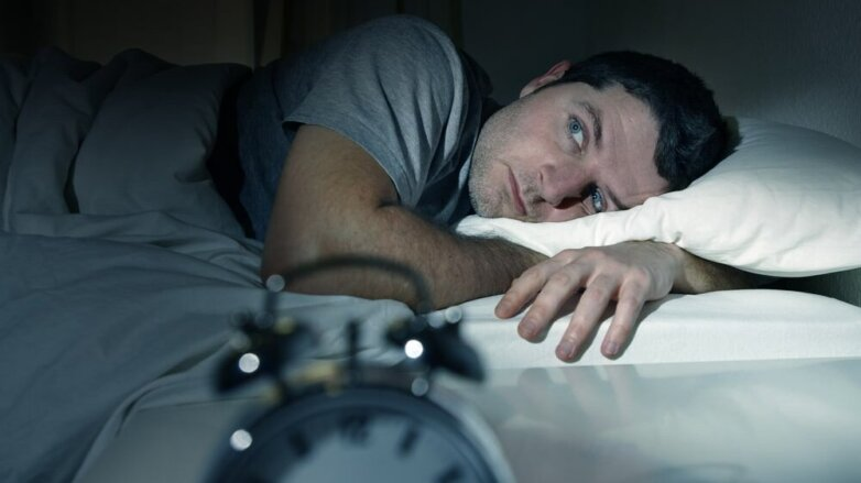 Мужчина в постели с открытыми глазами страдает бессонницей бессонница будильник кошмар