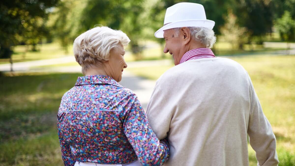 Счастливая пожилая пара на прогулке в парке пенсионеры