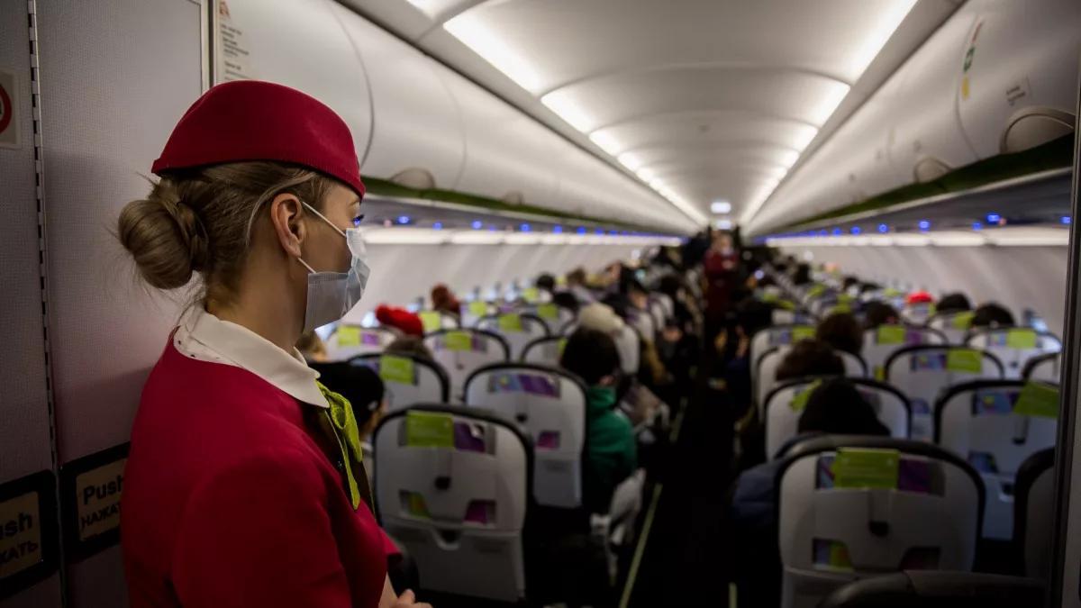 салон самолета и стюардесса в маске
