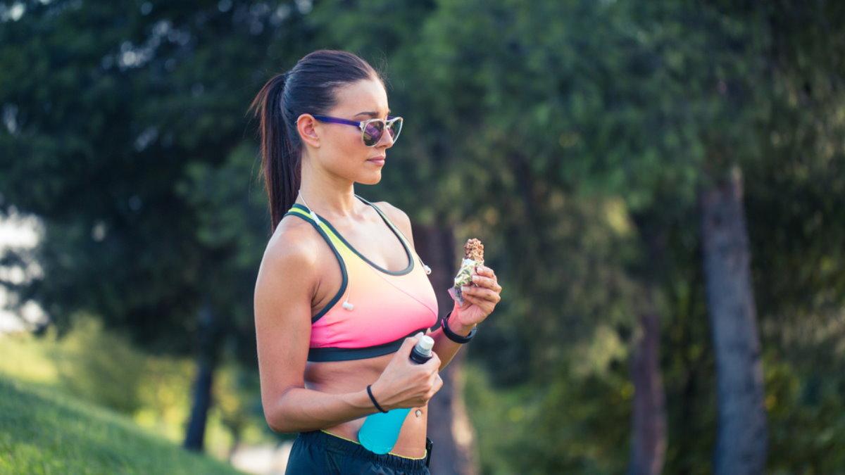 Девушка спортсменка энергетический протеиновый батончик спортивный напиток