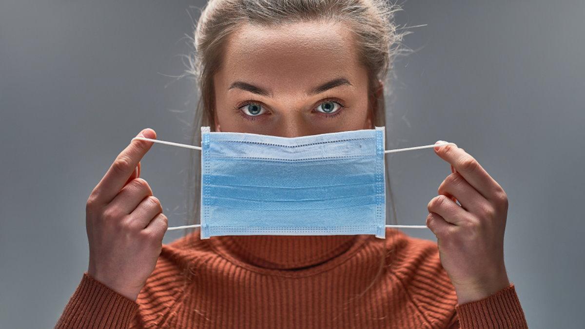 Девушка надевает снимает медицинскую маску медицинская маска коронавирус