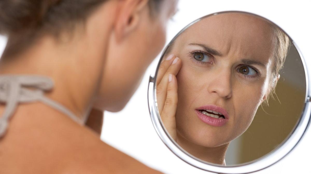 Женщина смотрит в зеркало красота морщины уход за кожей лица лицо