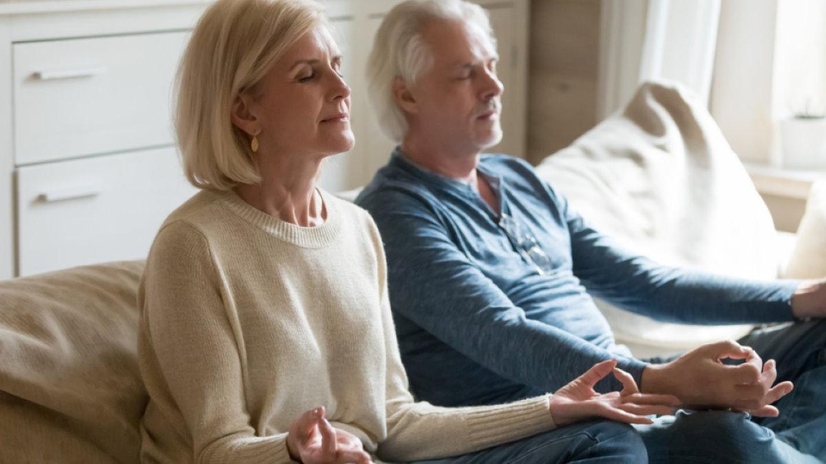 Пожилая пара медитирует дома медитация