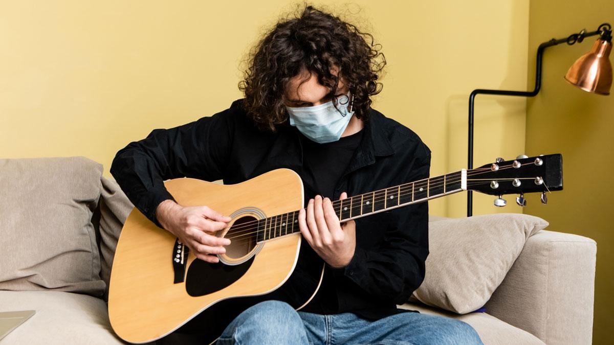 Человек в медицинской маске играет на акустической гитаре