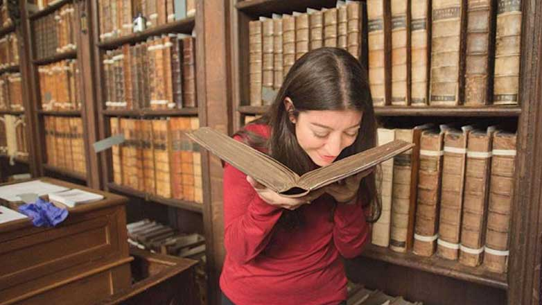 Женщина нюхает старую книгу
