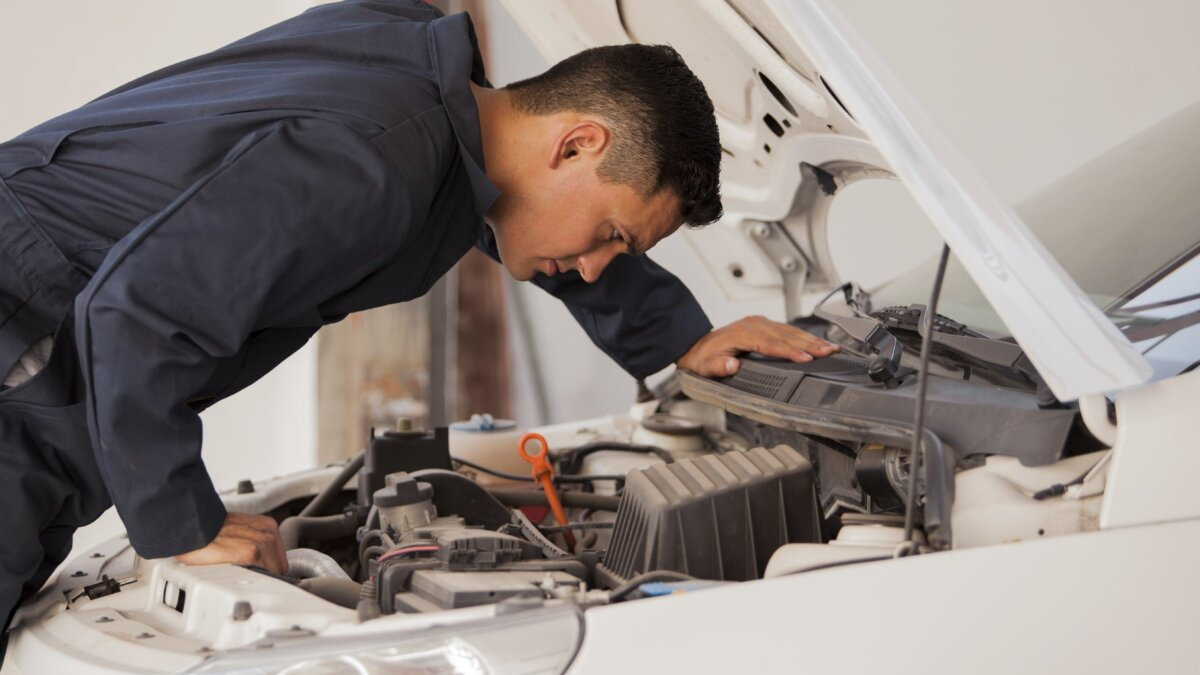 Мужчина смотрит под капот автомобиля.