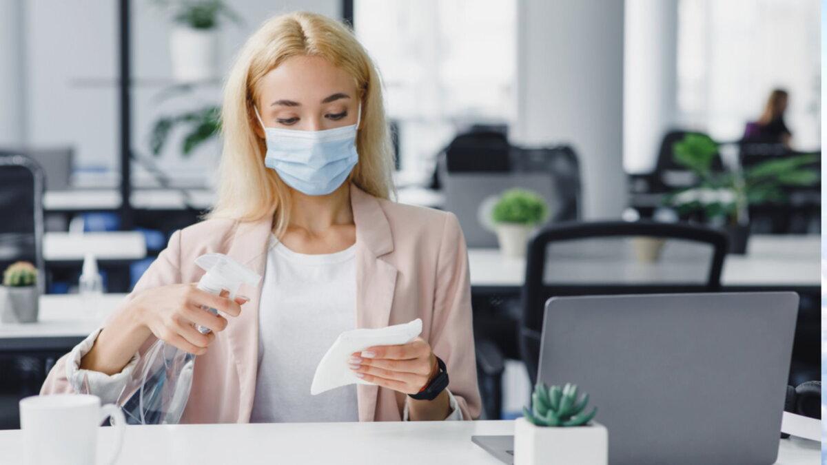Коронавирус девушка дезинфицирует рабочее место офис