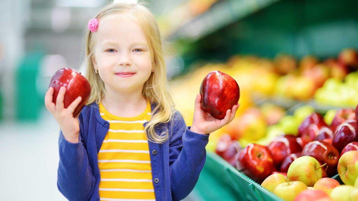 Девочка в магазине с яблоками apples selection
