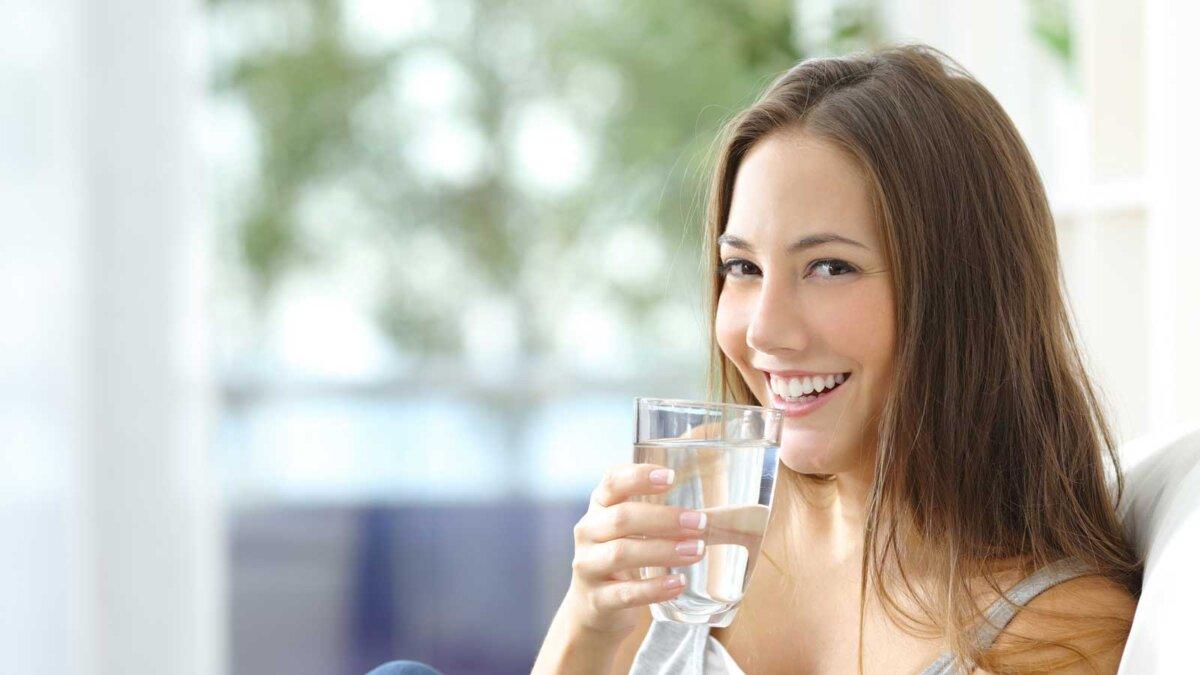 Девушка пьет воду стакан