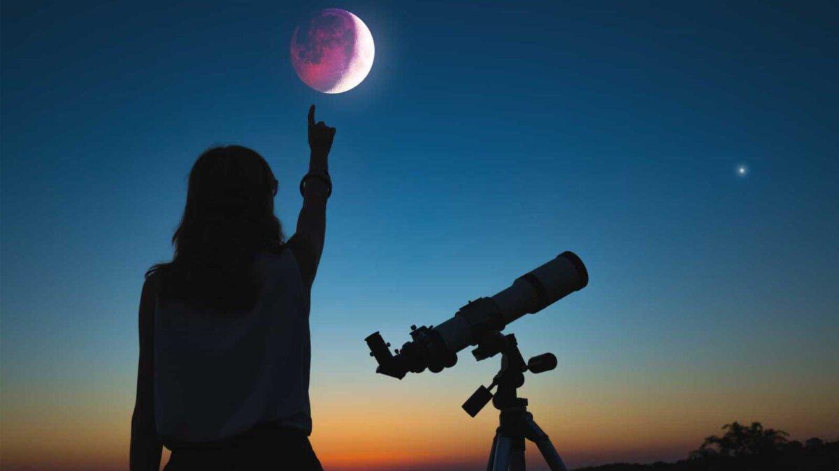 Девушка смотрит на лунное затмение через телескоп