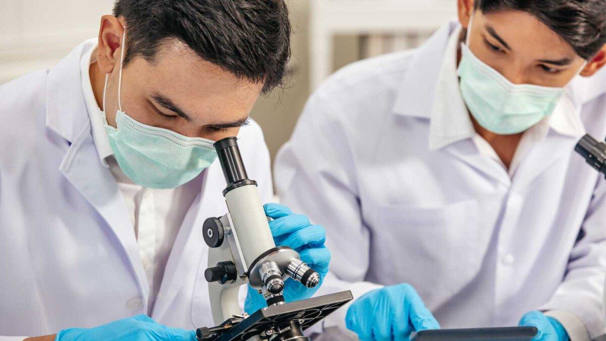 Два мужчины в масках работают в лаборатории Two Male Scientists wear Face Mask working in Lab