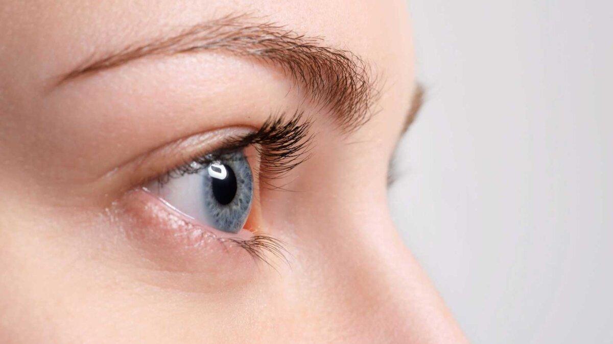 Крупный вверх синий глаз с естественным макияжем глядя в сторону, макрос выстрел с идеальной кожи