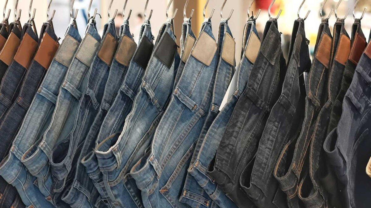 Много джинсов висит на стойке