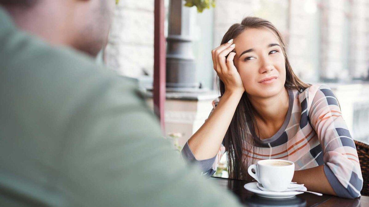 Молодая скучно девушка сидит и пьет кофе на свидании со своим парнем в кафе