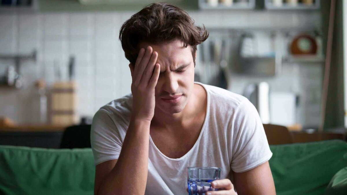 Молодой человек, страдающий от сильной головной боли