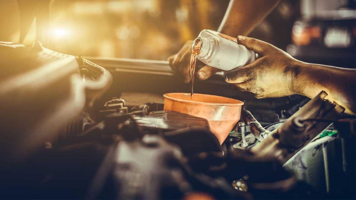 Мужчина наливает моторное масло engine oil