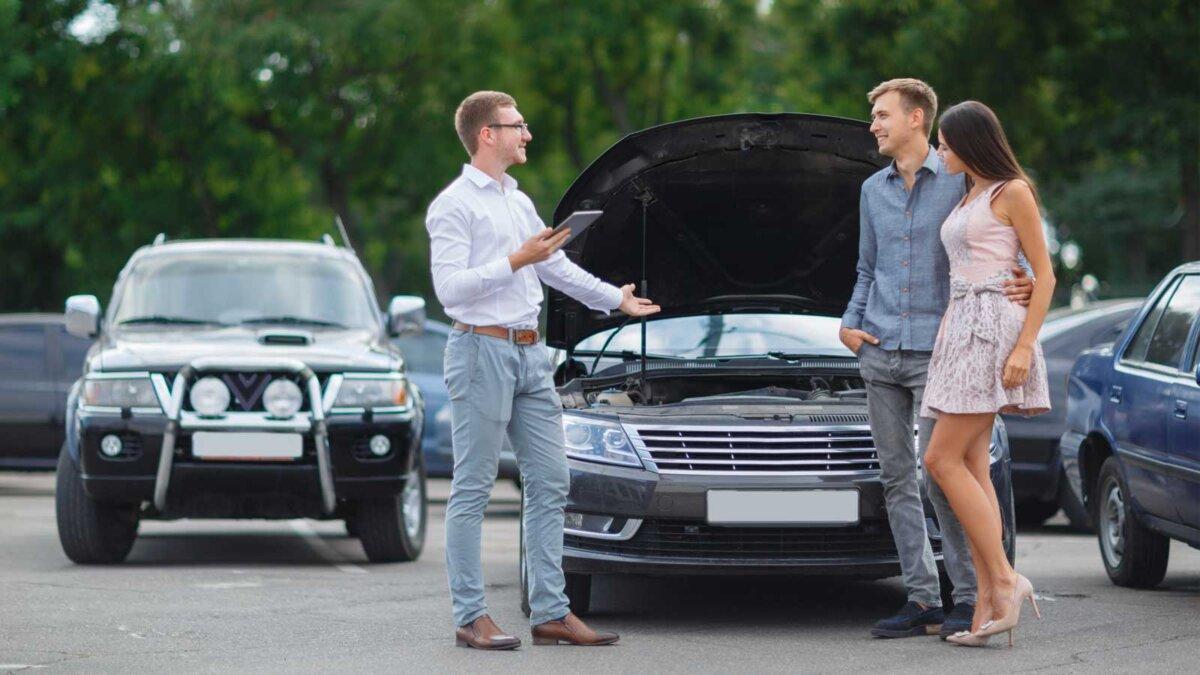 Мужчина продает подержанный автомобиль молодой паре открыт капот