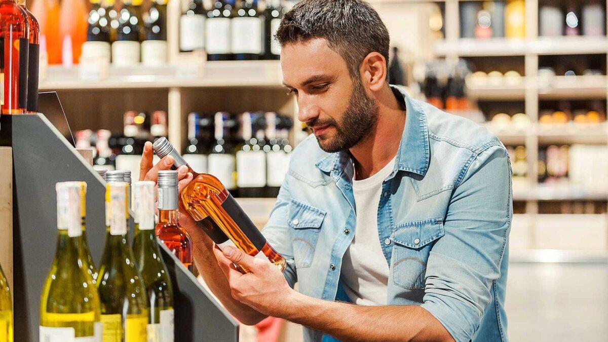 Мужчина выбирает алкголь магазин Handsome young man holding bottle of wine