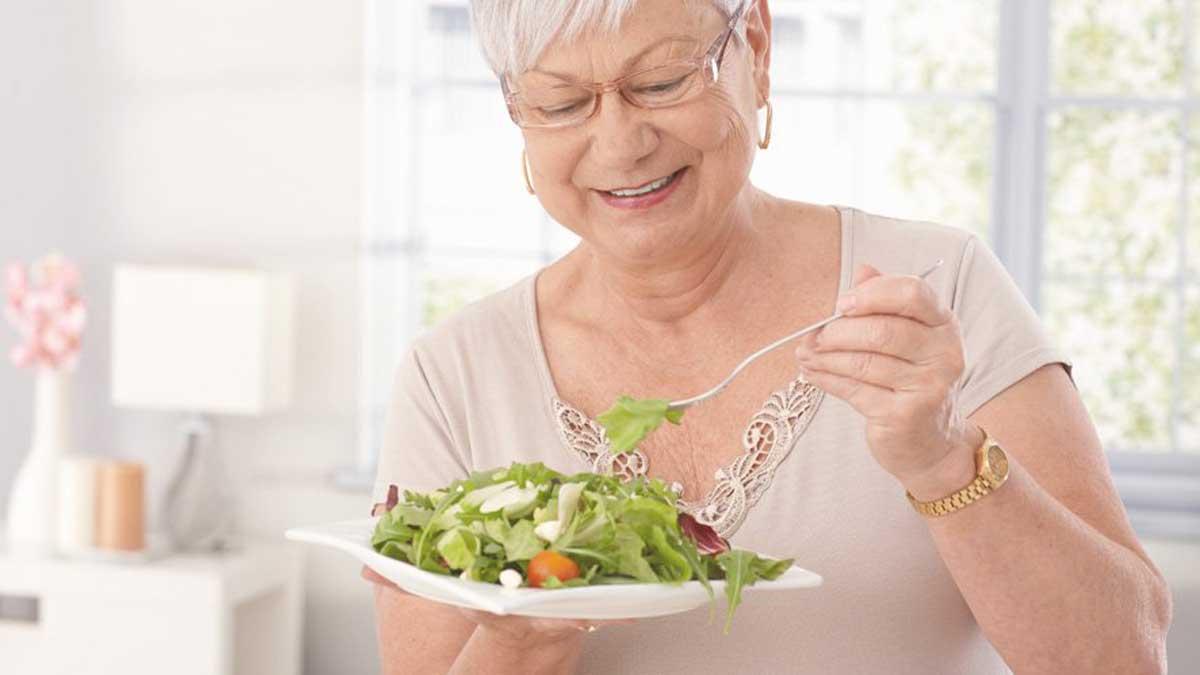 Пожилая женщина ест зелень