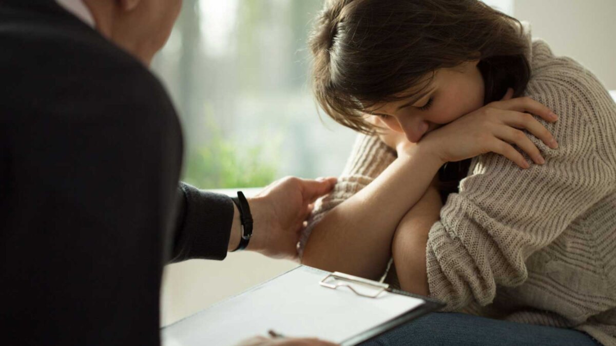 Психолог девушка беспокойство Professional psychiatrist comforting crying patient with mental disorder