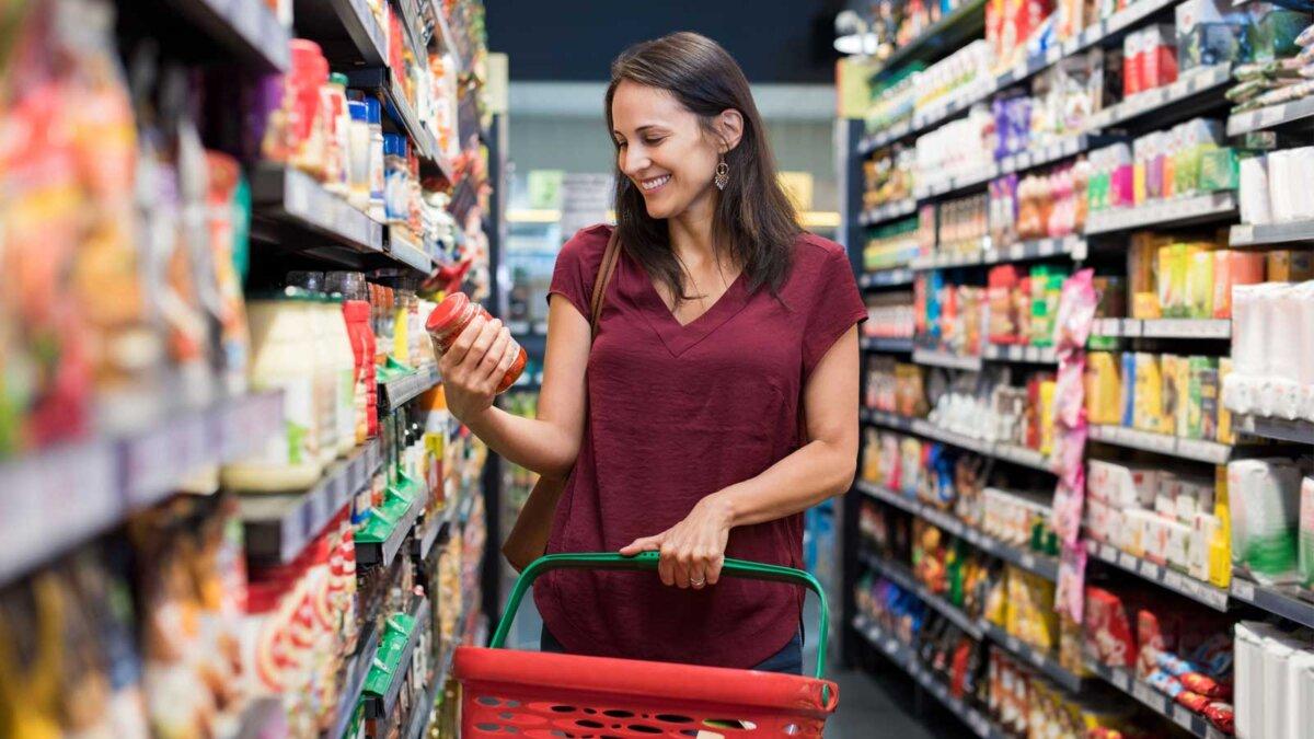 Счастливая женщина смотрит на продукт в продуктовый магазин
