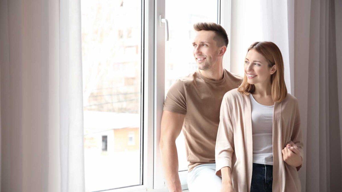 Счастливые парень девушка смотрят в пластиковые окна Happy smiling couple near plastic window