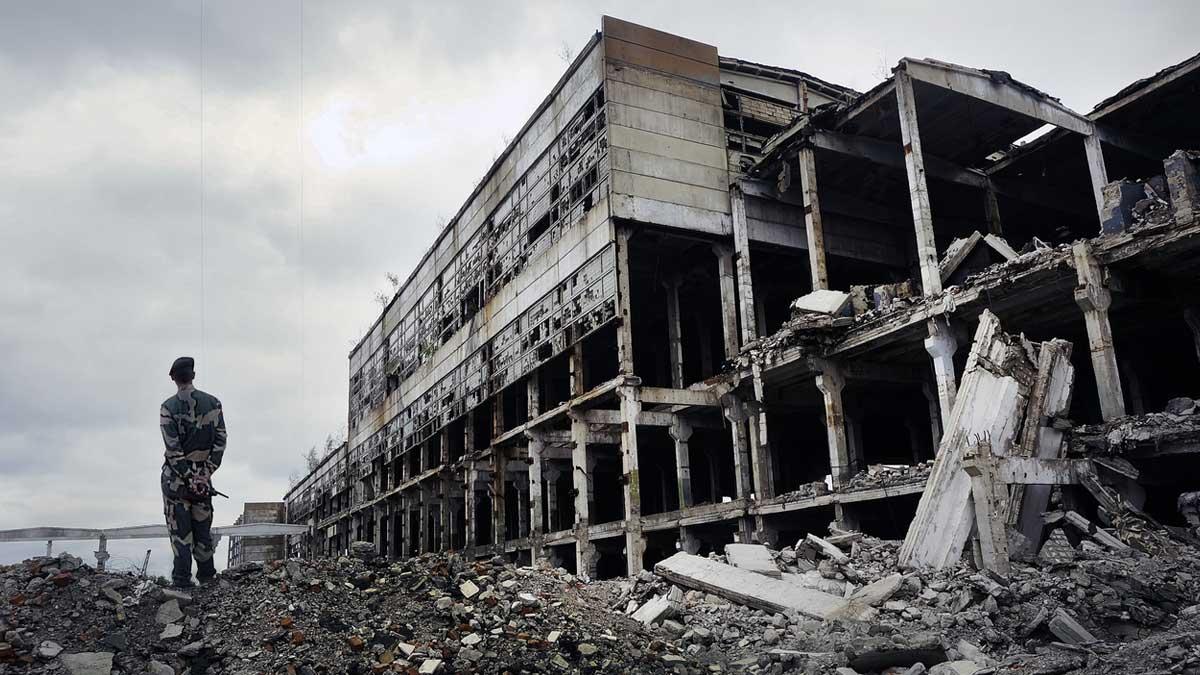 Солдат в военной форме стоит на руинах разрушенного дома