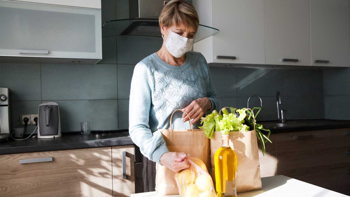 Женщина дома в маске думает пакеты с едой