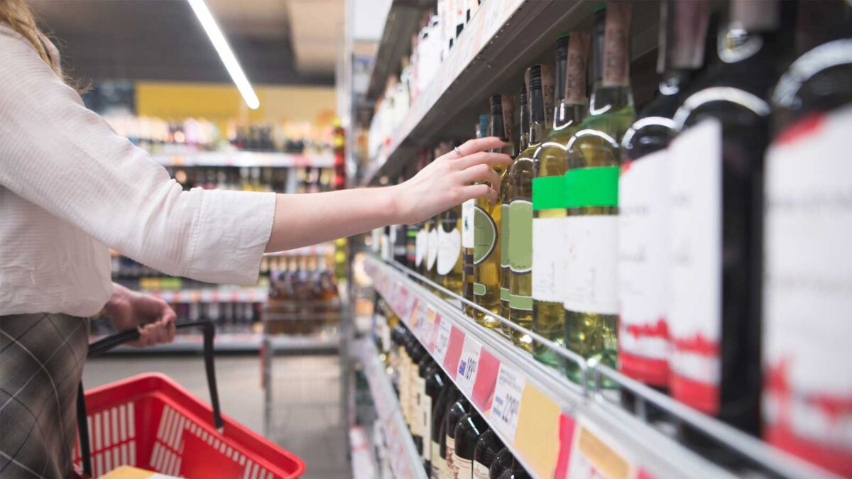Женщина рука алкоголь Woman's hand takes a bottle of wine