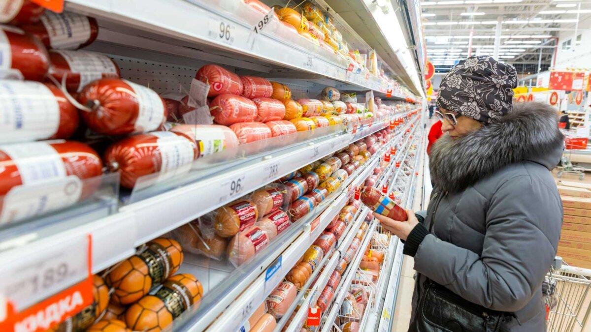 Женщина выбирает докторскую колбасу a woman chooses sausage in a store