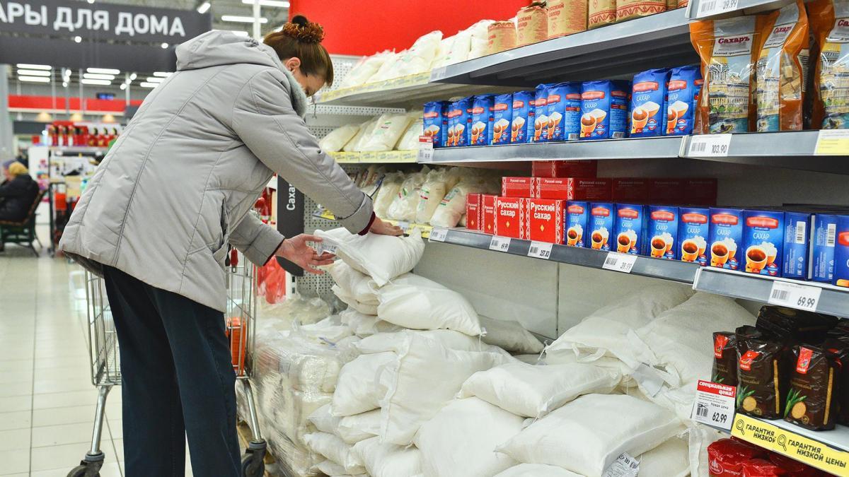 покупательница берет сахар в магазине