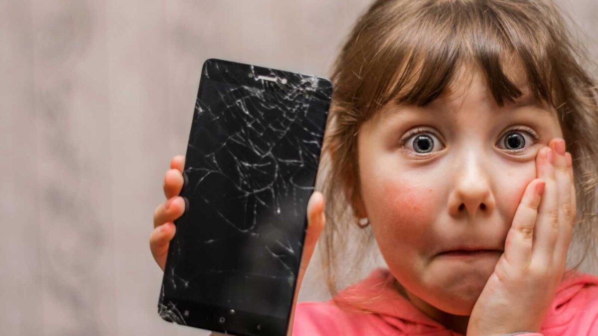маленькая девочка держит поломанный телефон A sad child broke the screen of a mobile phone