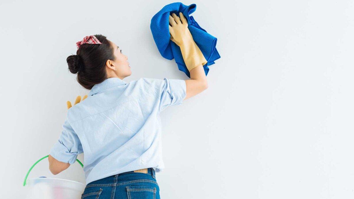 молодая женщина в защитных перчатках очищая стену