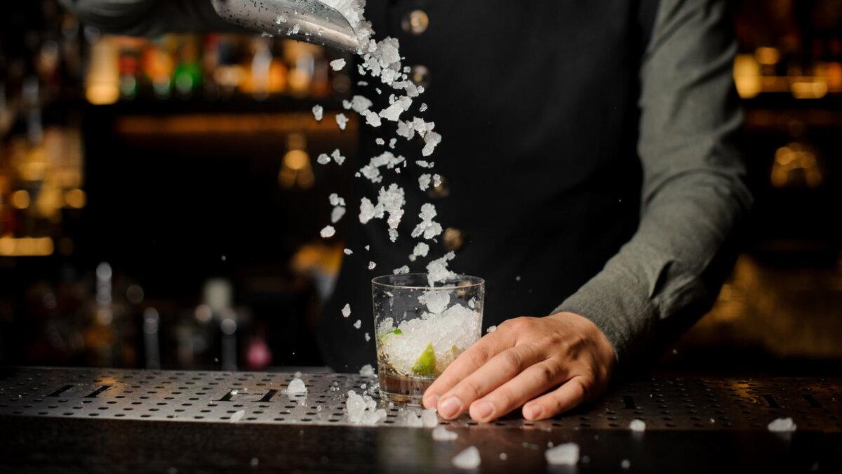 Алкоголь бармен добавляет лёд в коктейль