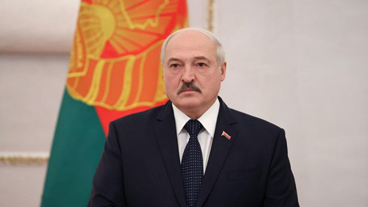 Александр Лукашенко на фоне флага