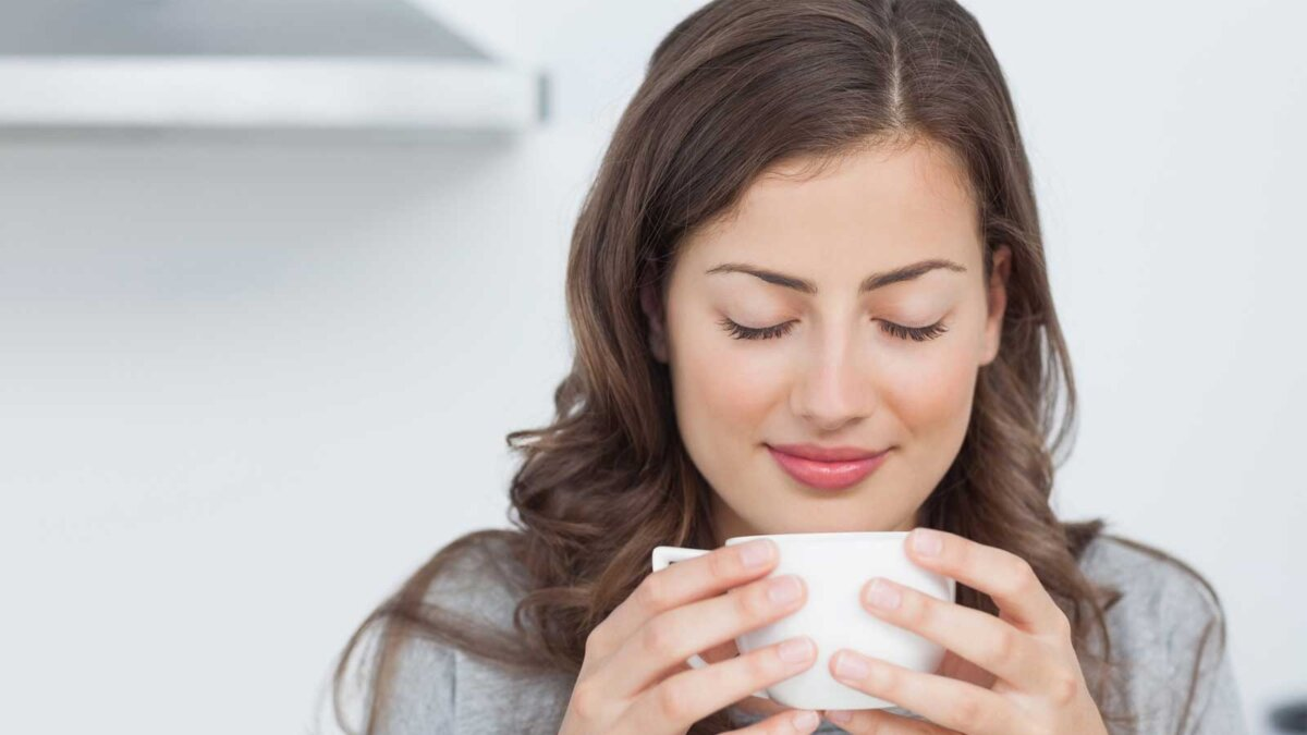 Девушка нюхает запах утреннего кофе