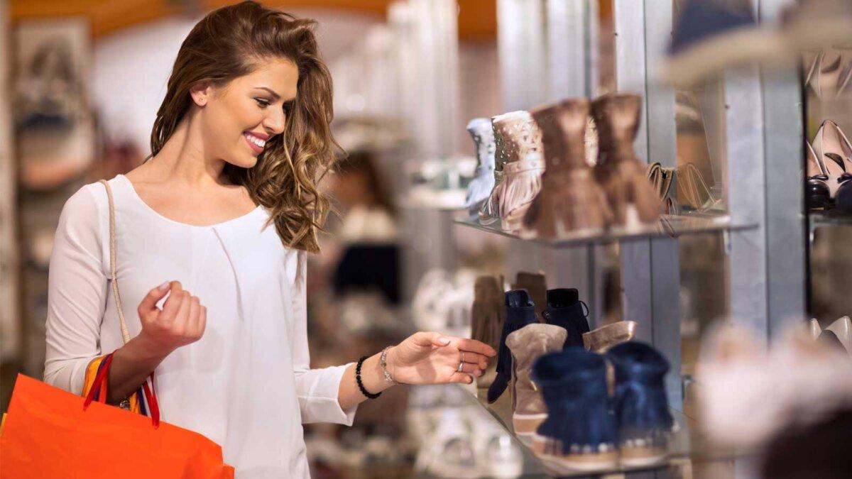 Девушка покупает обувь в магазине
