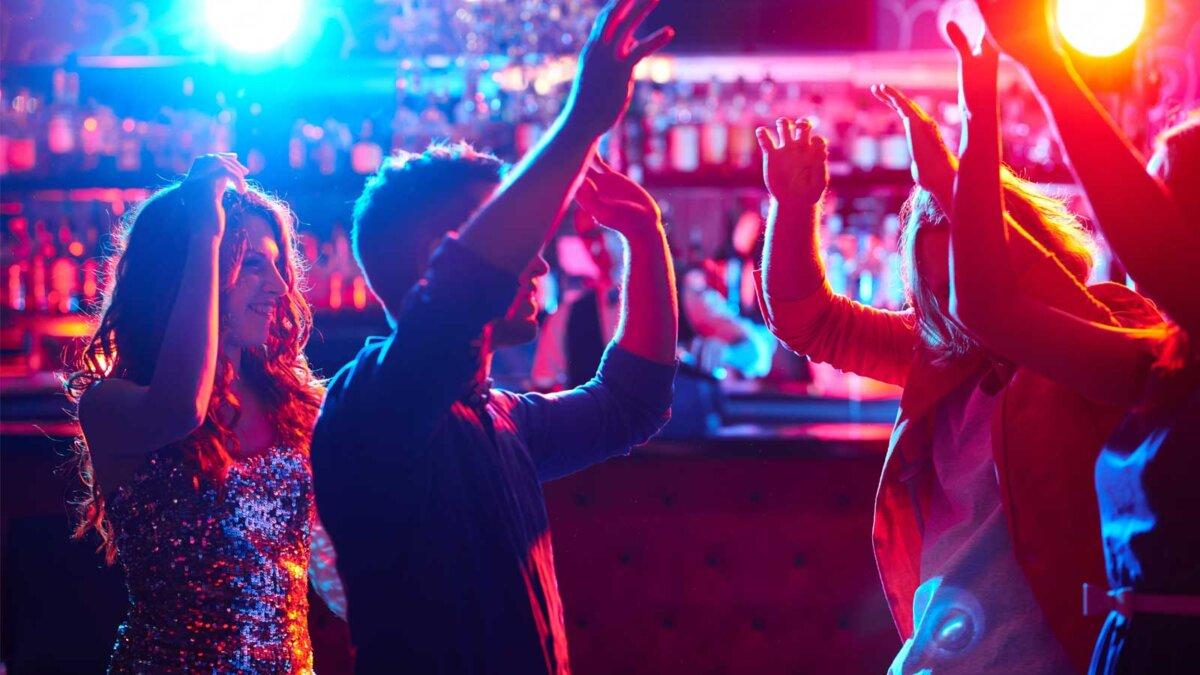 Энергичные друзья танцуют в ночном клубе