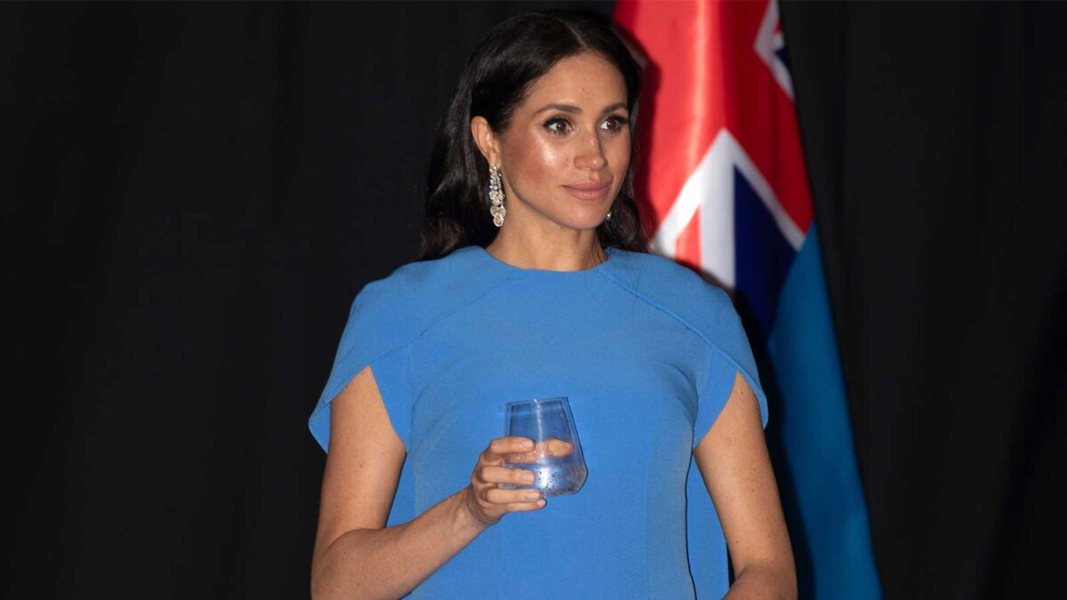 Герцогиня Сассекская Меган Маркл со стаканом в руке на фоне флага Великобритании