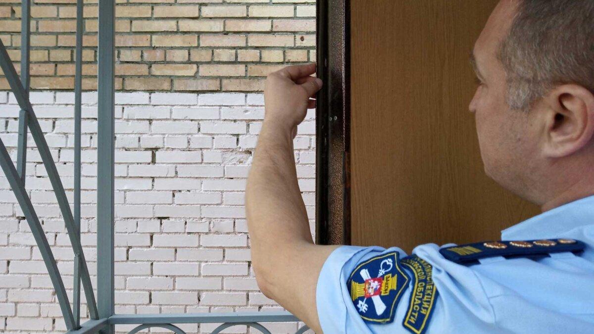 Работник Жилинспекции стоит возле двери