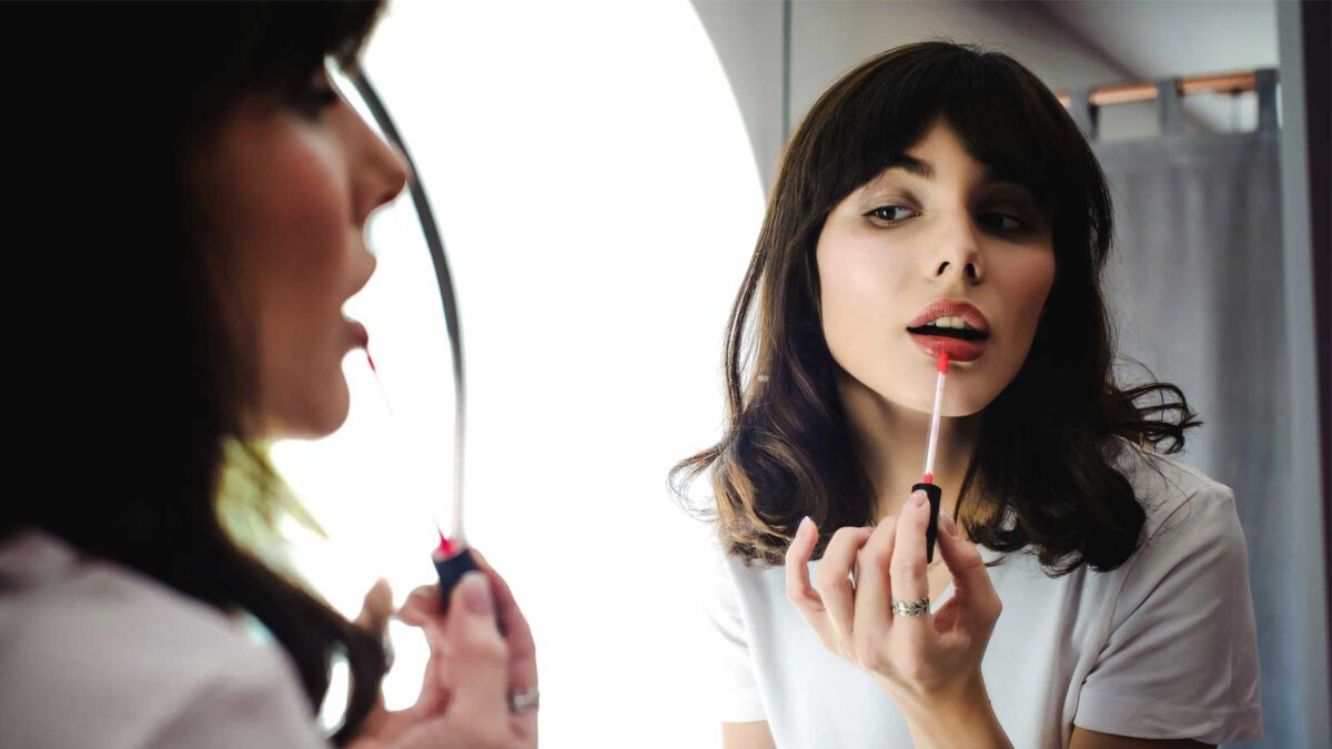 Красивая девушка красит губы глядя в зеркало beautiful woman, dyes her lips lipstick pink, looking in the mirror