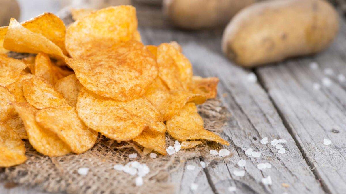 Куча картофельных чипсов паприки на деревенском фоне